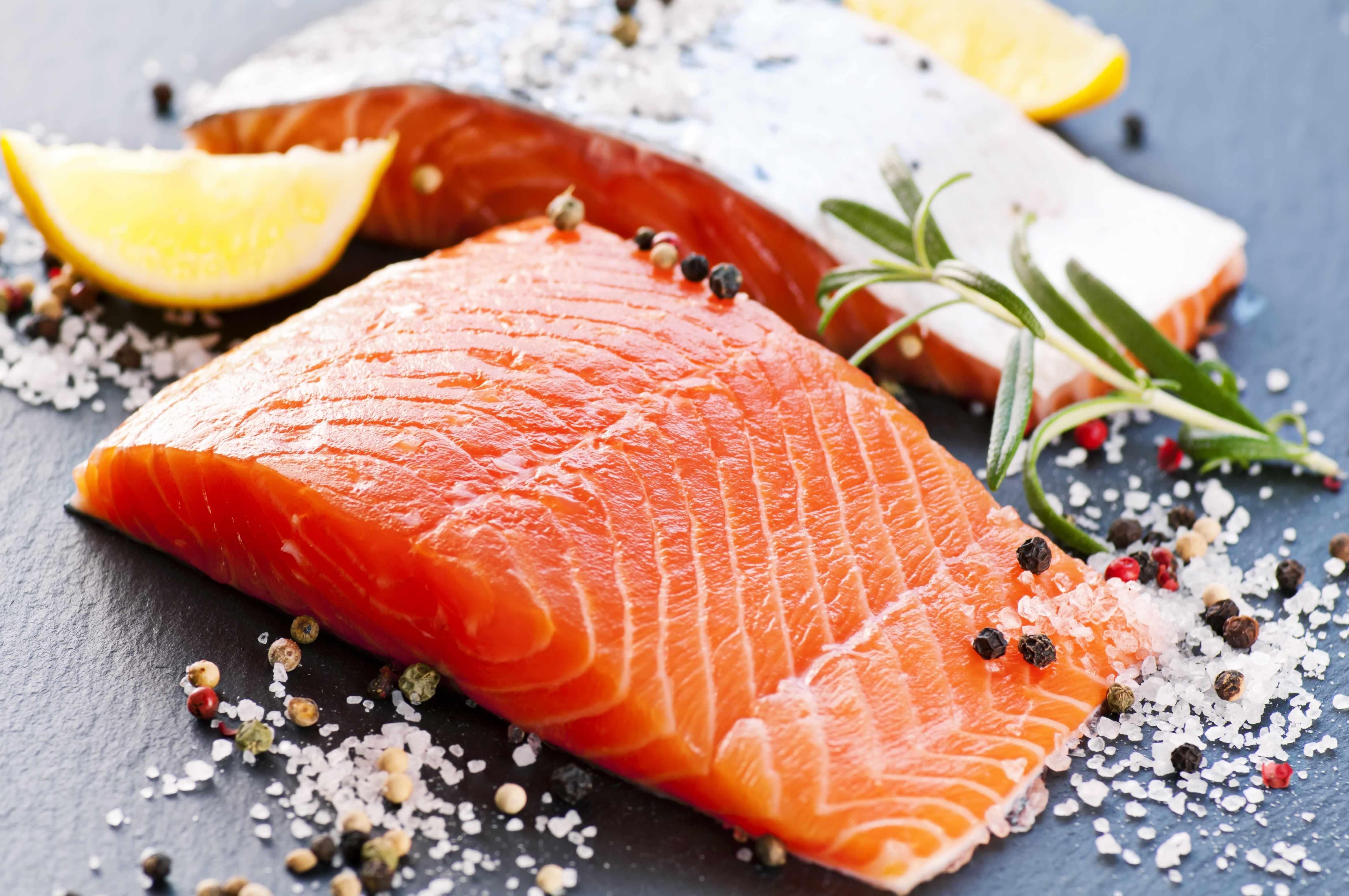 a fresh slice of salmon with lemon, sea salt and herbs