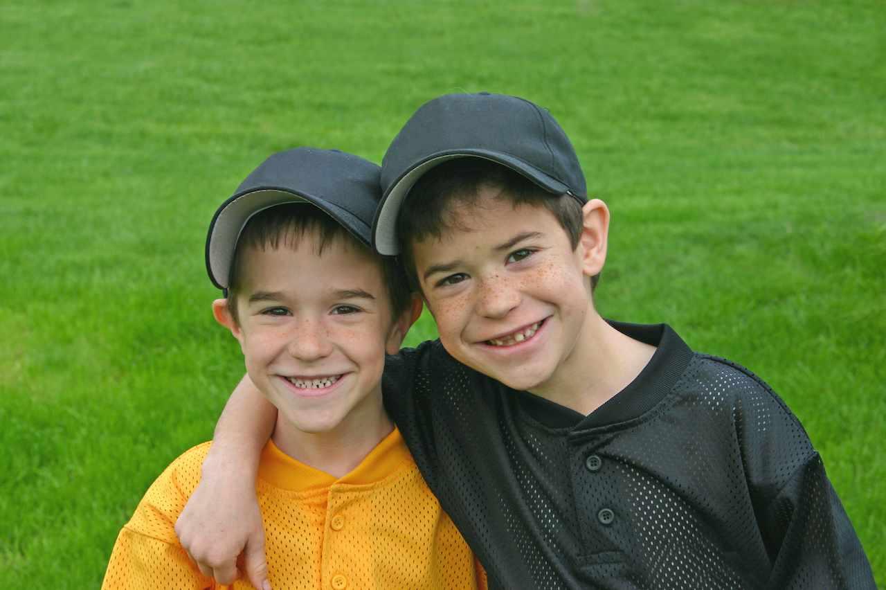 two little boys on a sports field wearing baseball caps