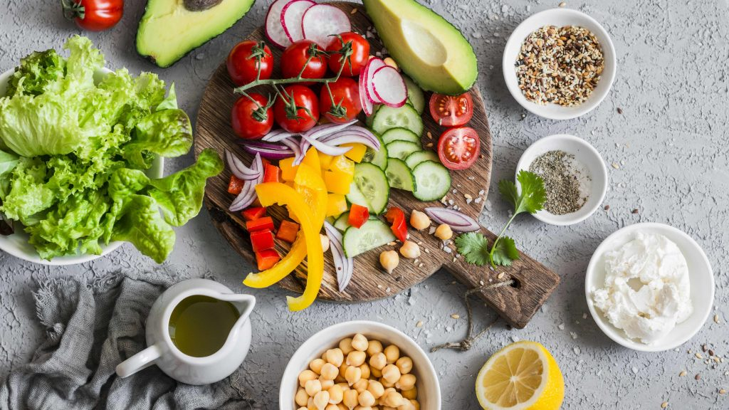 Ingredients for a healthy vegetable salad with lettuce, chickpeas and avocados