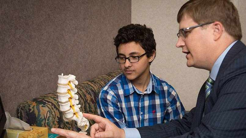 patient Albert Mansour with Dr. Todd Milbrandt looking at spinal cord model
