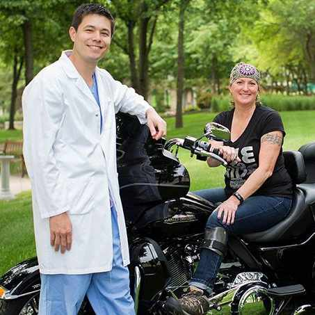 patient Sue Bothun on a motorcycle with Dr. Brandon Yuan standing near