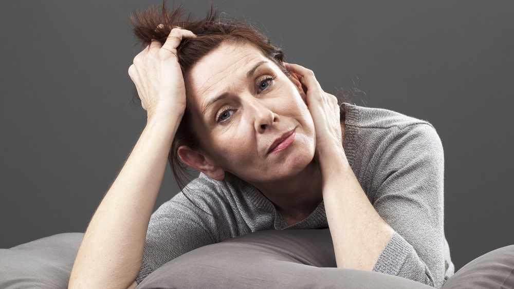 Una mujer cansada sobre unos cojines