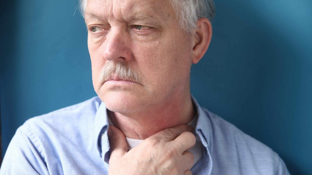 a close-up of an older man with his hand to his throat, looking very uncomfortable, perhaps feeling something is stuck in his throat
