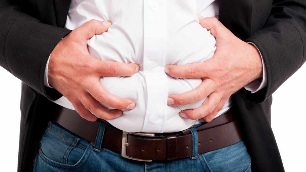 Un hombre aprieta su estómago porque tiene dolor o gases