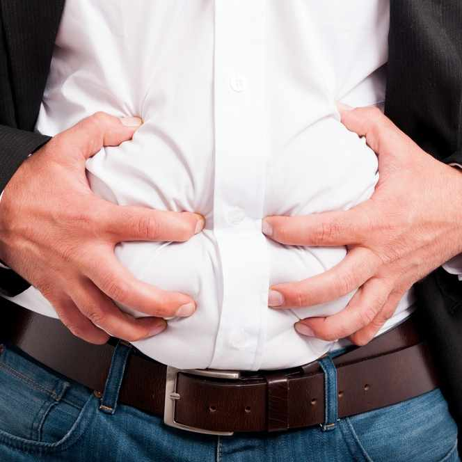 a man holding or grabbing his stomach as if having belly pain or gas