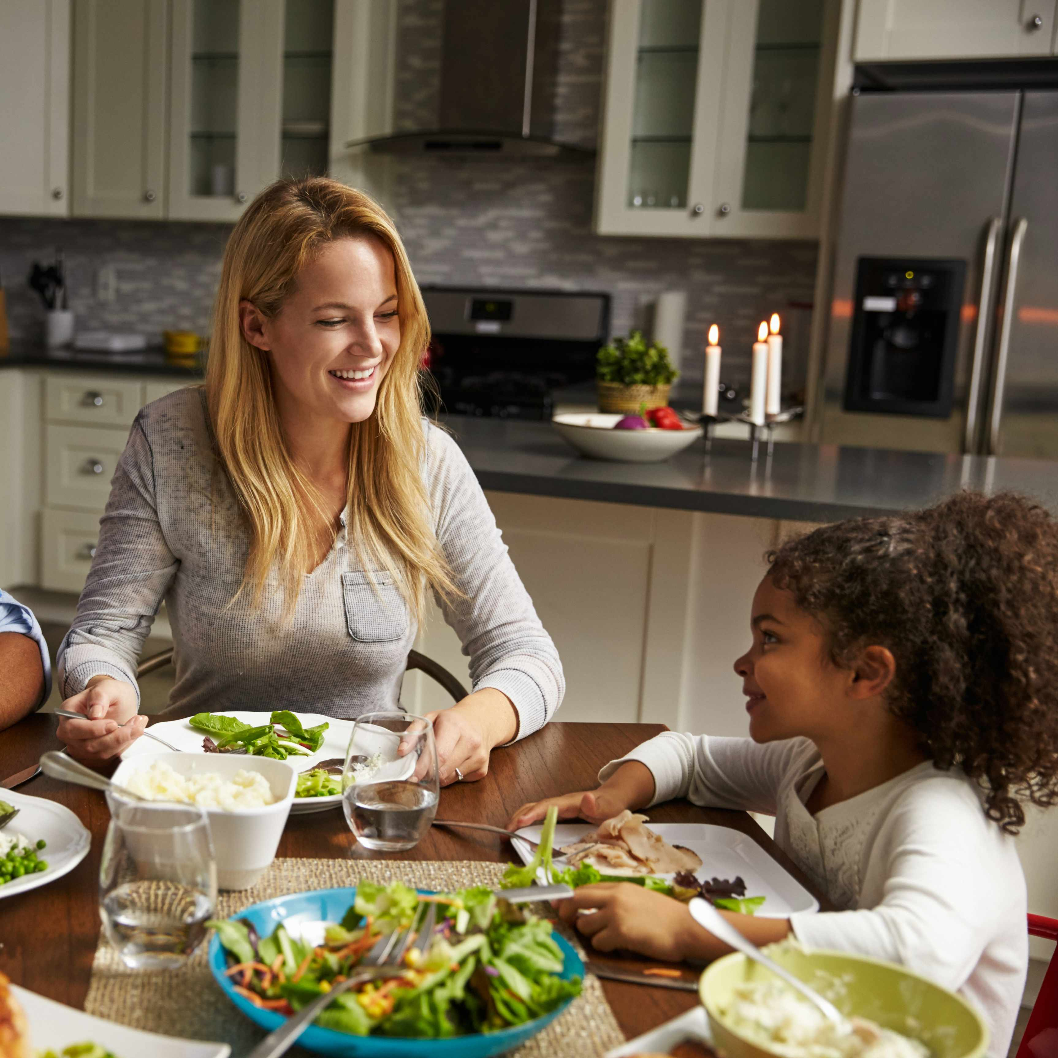 an adult woman, mother sitting at a family dinner table with daughter, little girl