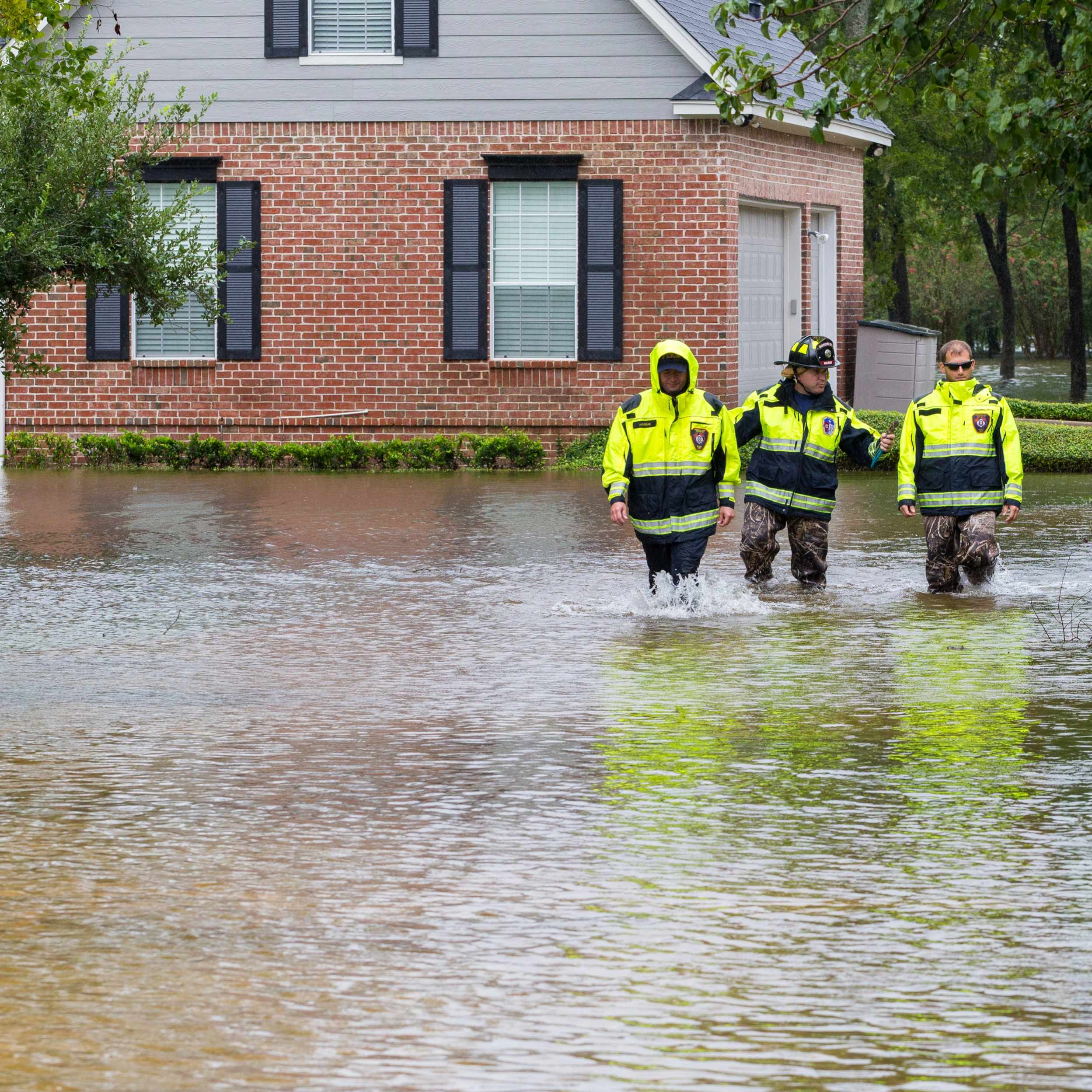 emergency workers walking through flood waters after the storm