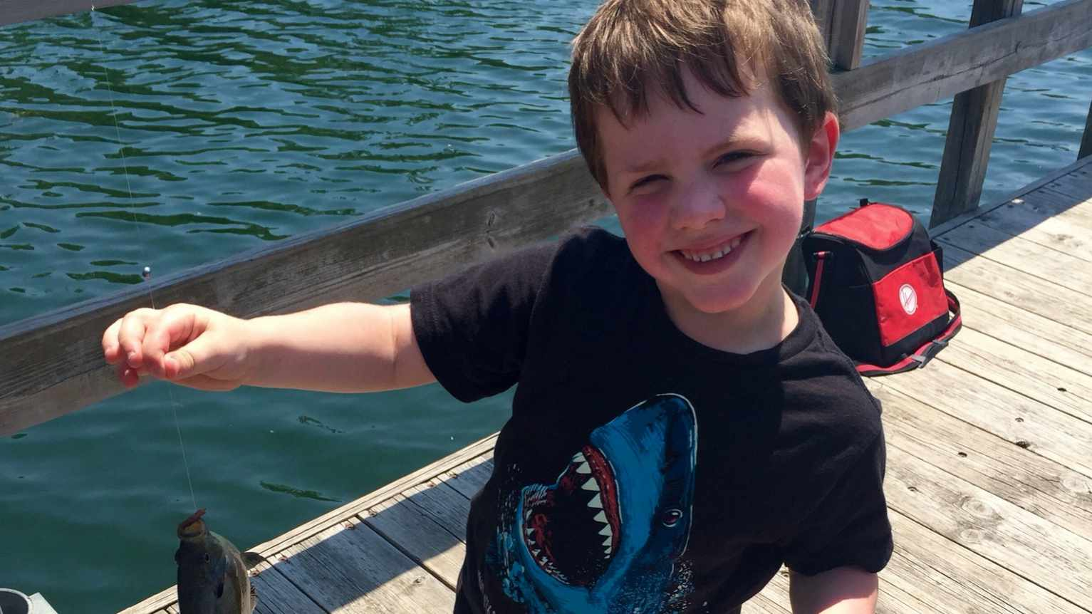 patient Gus on a fishing dock smiling and holding a fish