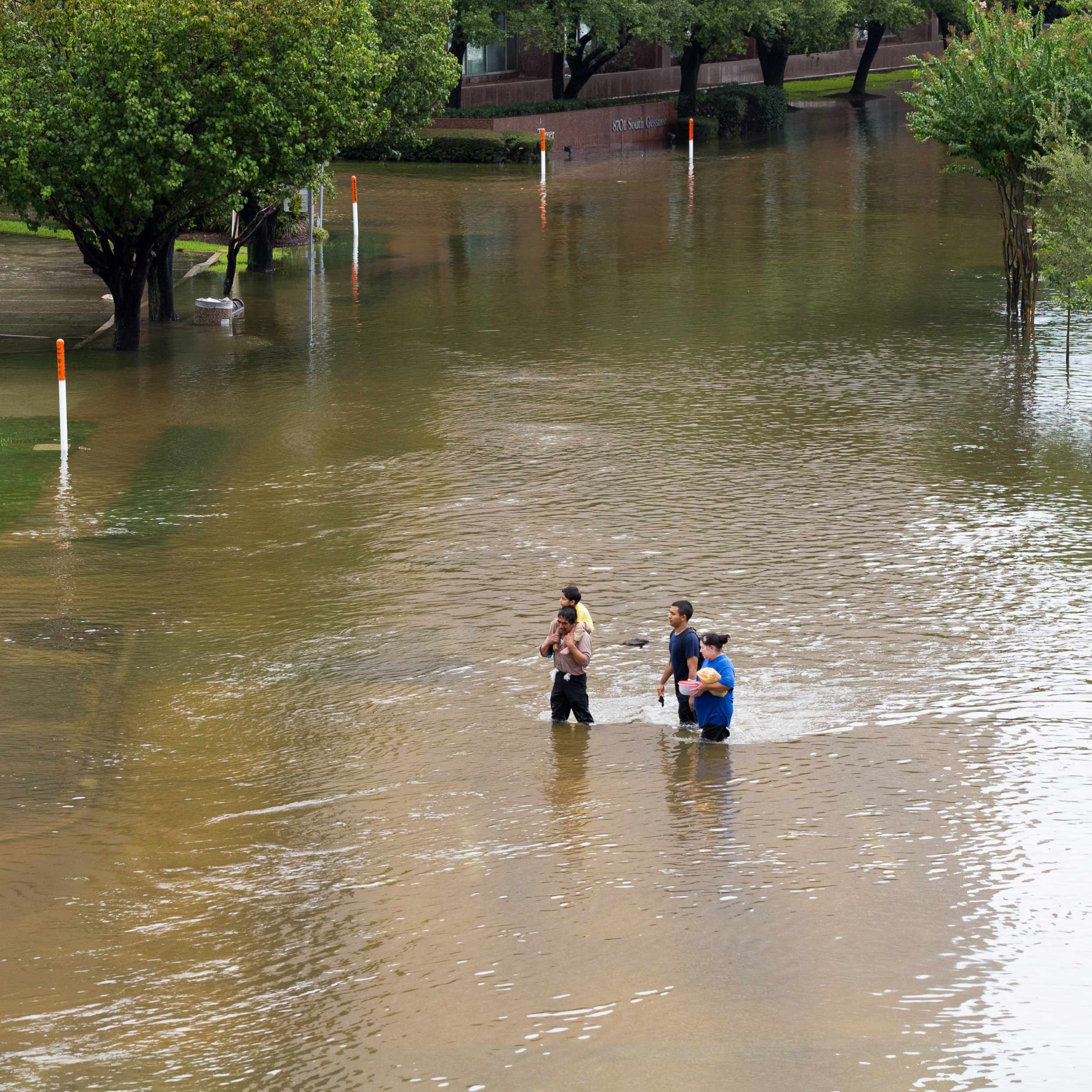 people walking through floodwaters in Houston after Hurricane Harvey