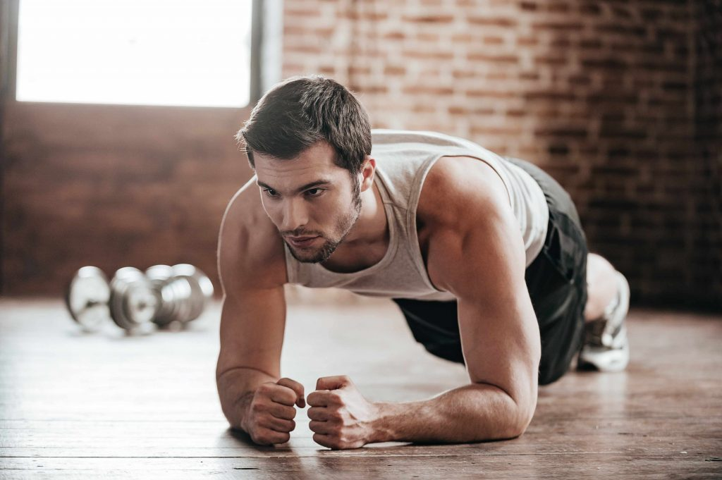 a young man in a gym, doing plank exercises for core muscle muscle development
