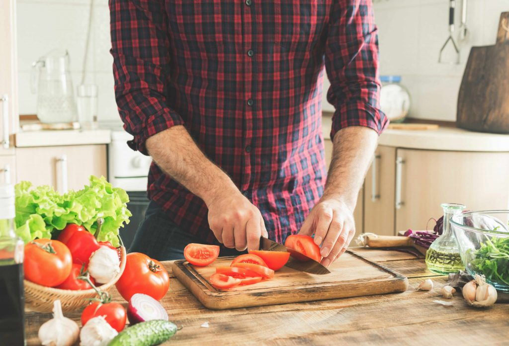 a man in a kitchen cutting tomatoes and other healthy vegetables for a salad dish