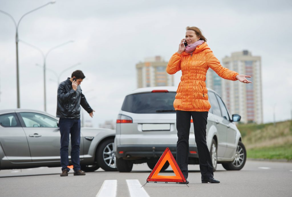 Choque automovilístico: dos conductores examinan los daños en los vehículos después de un accidente en la ciudad