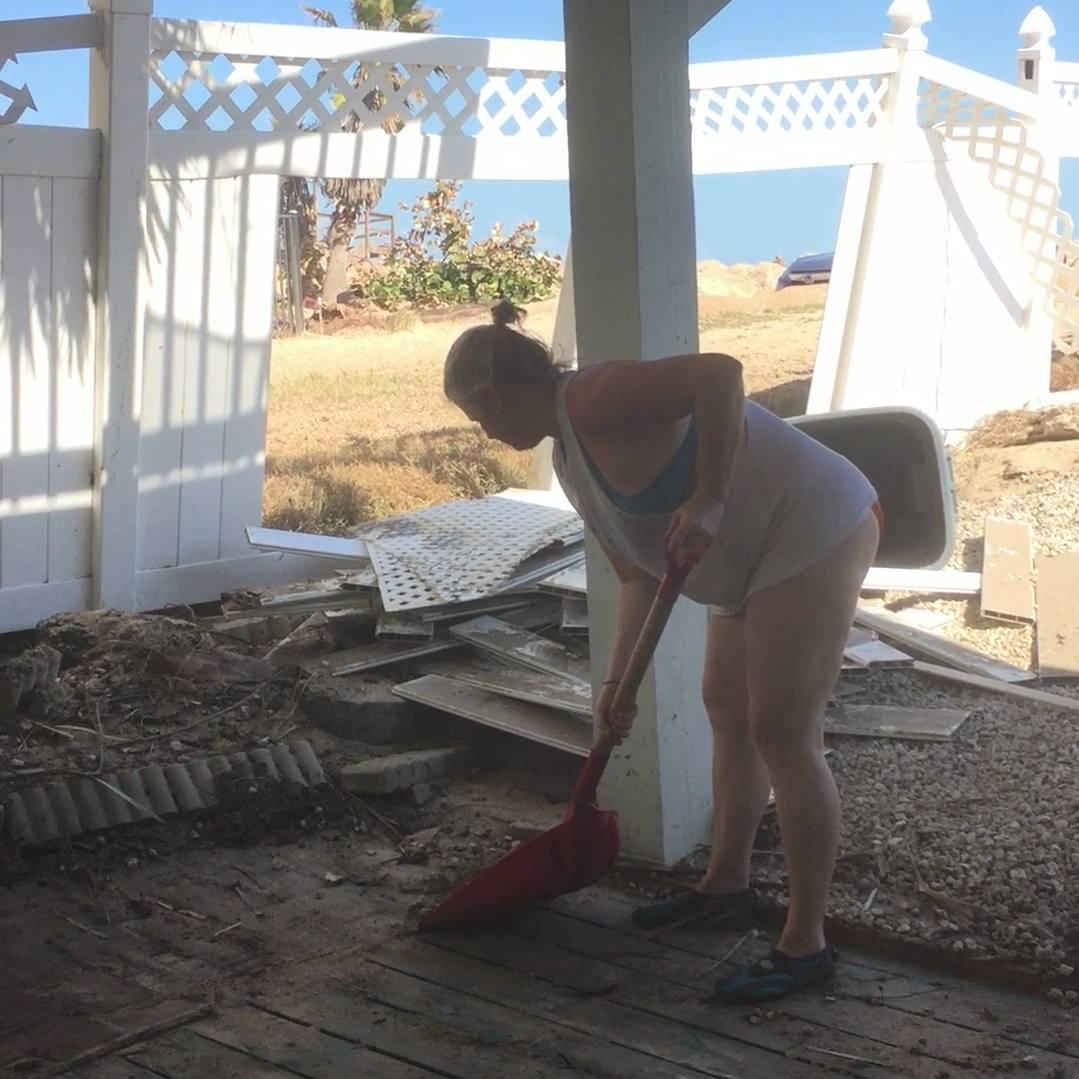 Woman shoveling debris left behind by hurricane Irma