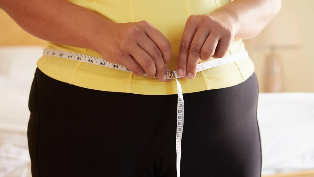 Una mujer mide su cintura