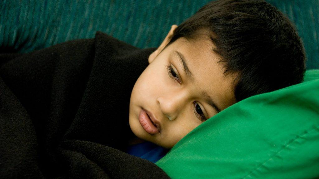 Un niño enfermo y muy bien parecido descansa