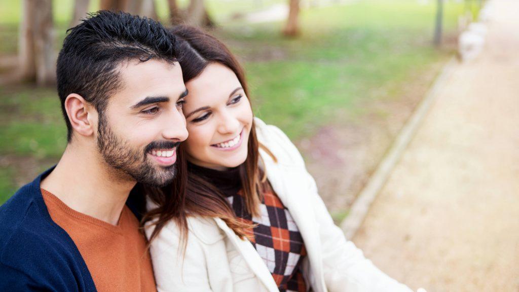 Una pareja enamorada está sentada en una banca del parque