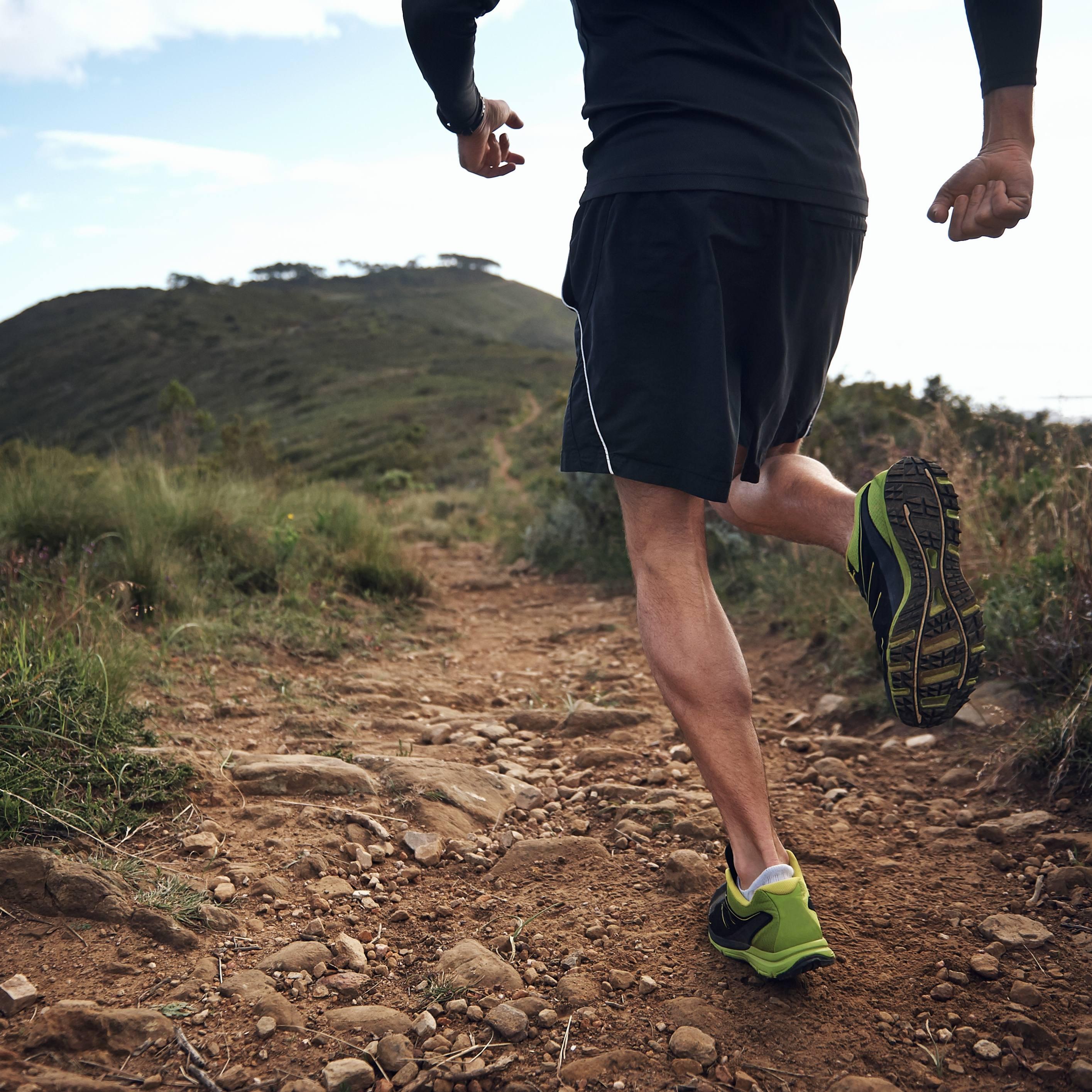 a man running a rocky dirt path in an endurance race on a hillside
