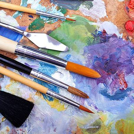 a painters palette full of paint colors and a number of paint brushes