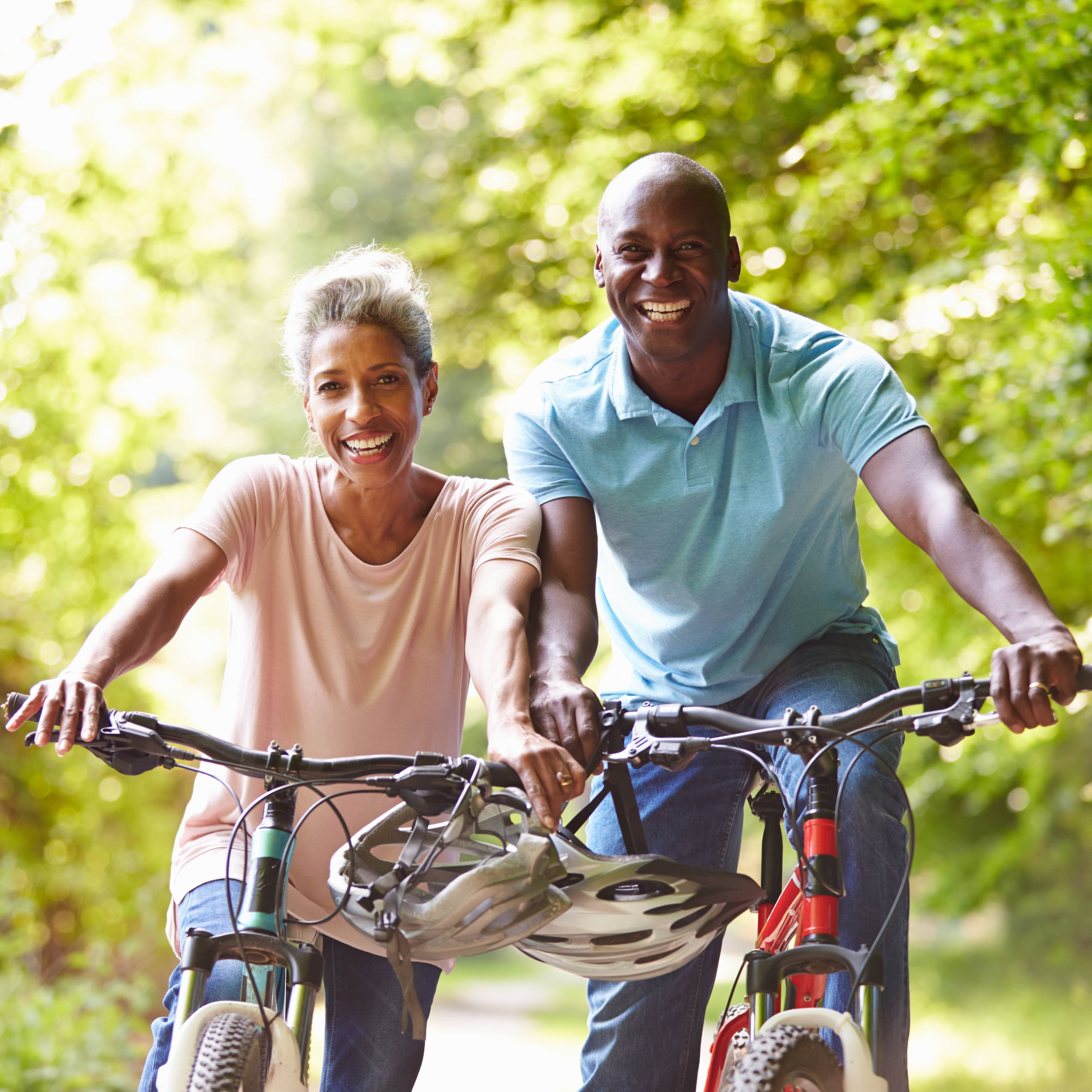 a smiling middle-aged couple on bicycles