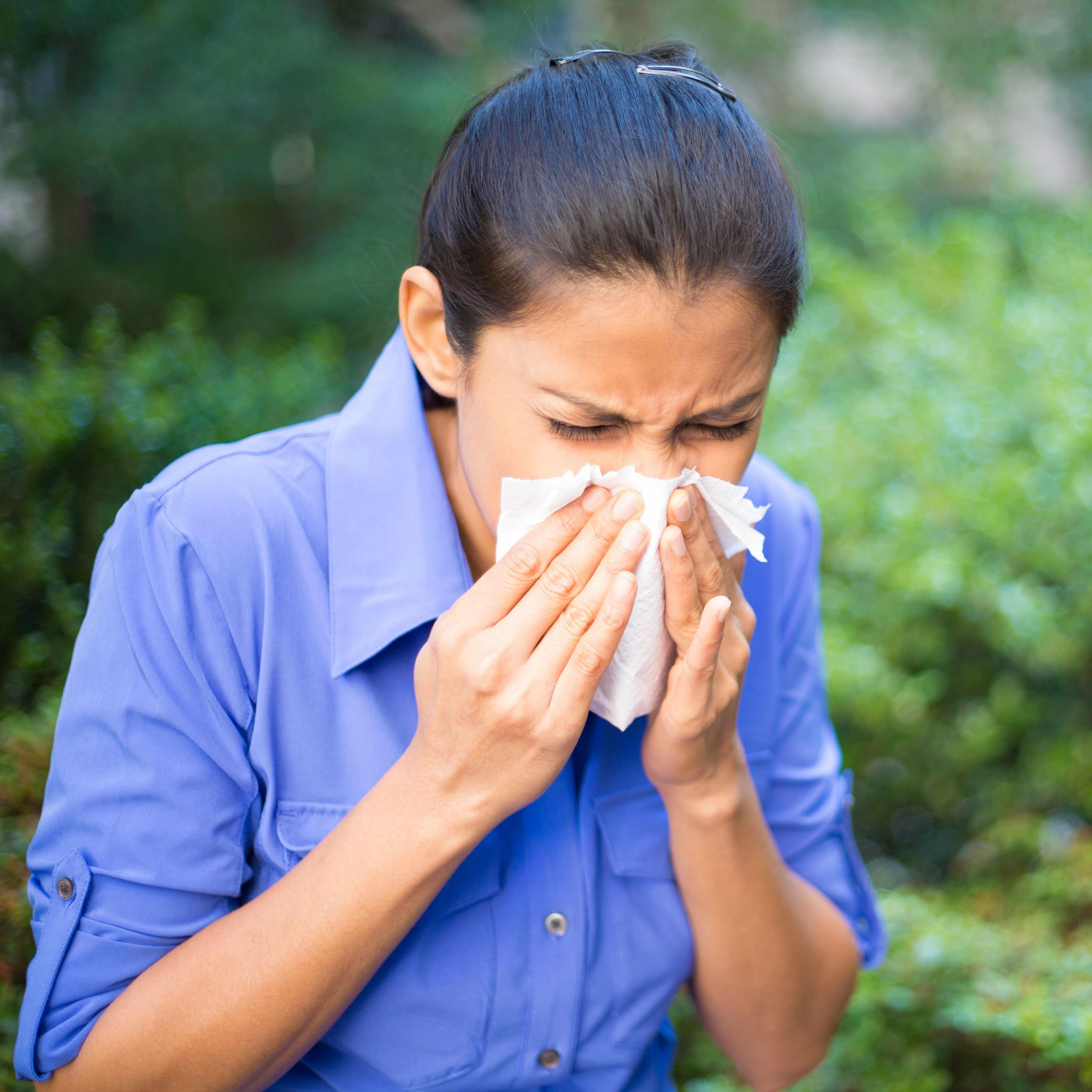 a woman blowing her nose into a tissue, sneezing
