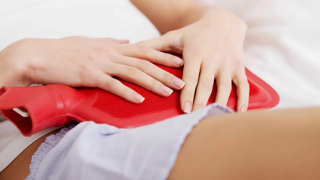 a woman holding a hot water bottle, for heat, on her stomach because of pain, menstrual cramps