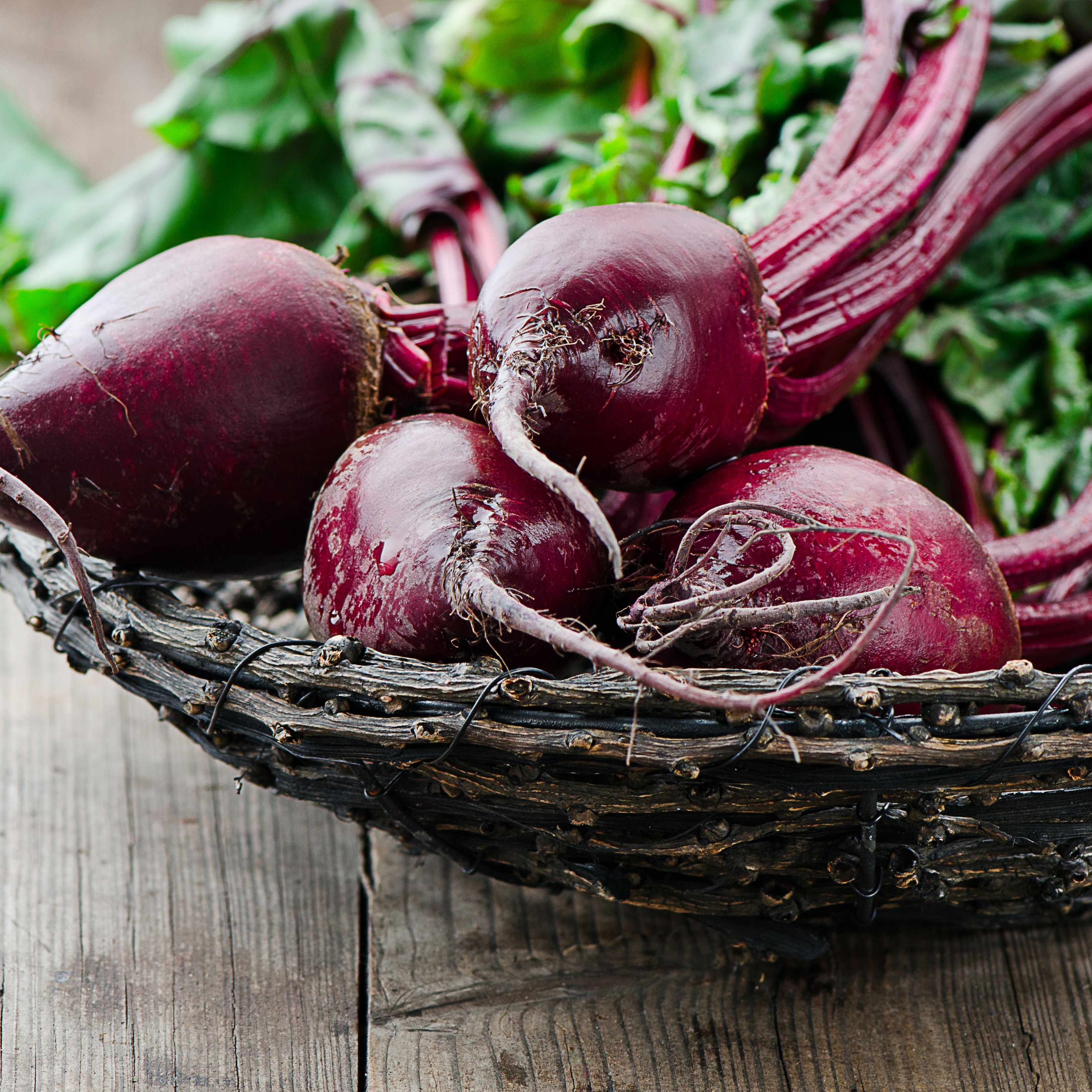 a bunch of fresh, red beets with green leaves in a wicker basket