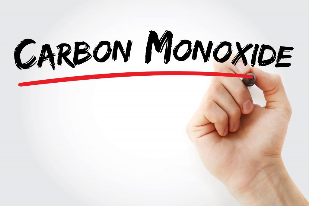 a hand holding a marker and writing the words carbon monoxide