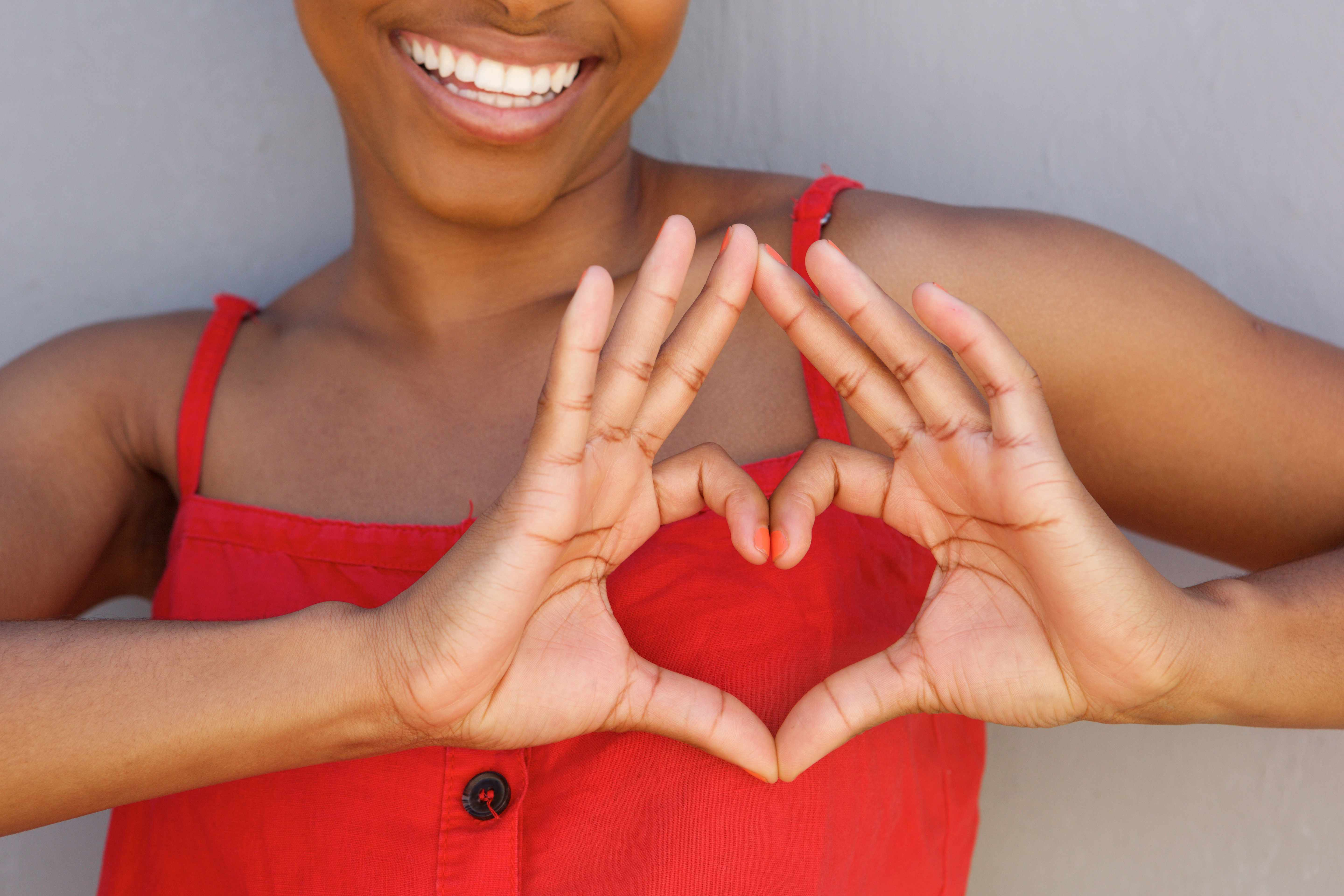 a woman in a red shirt smiling and forming her hands in the shape of a heart