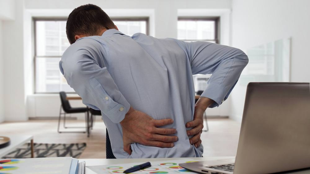 Businessman at desk with back pain