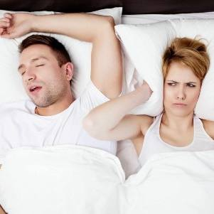 woman covering her ears from man snoring