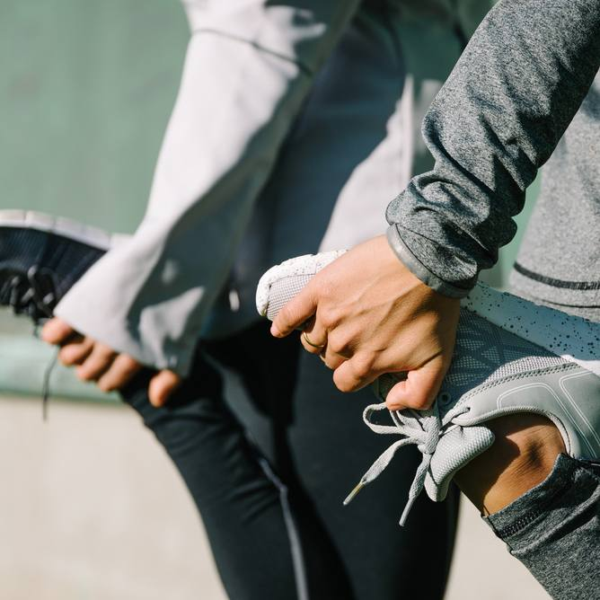 a close-up of the hands and feet of two women doing quadriceps stretching before running