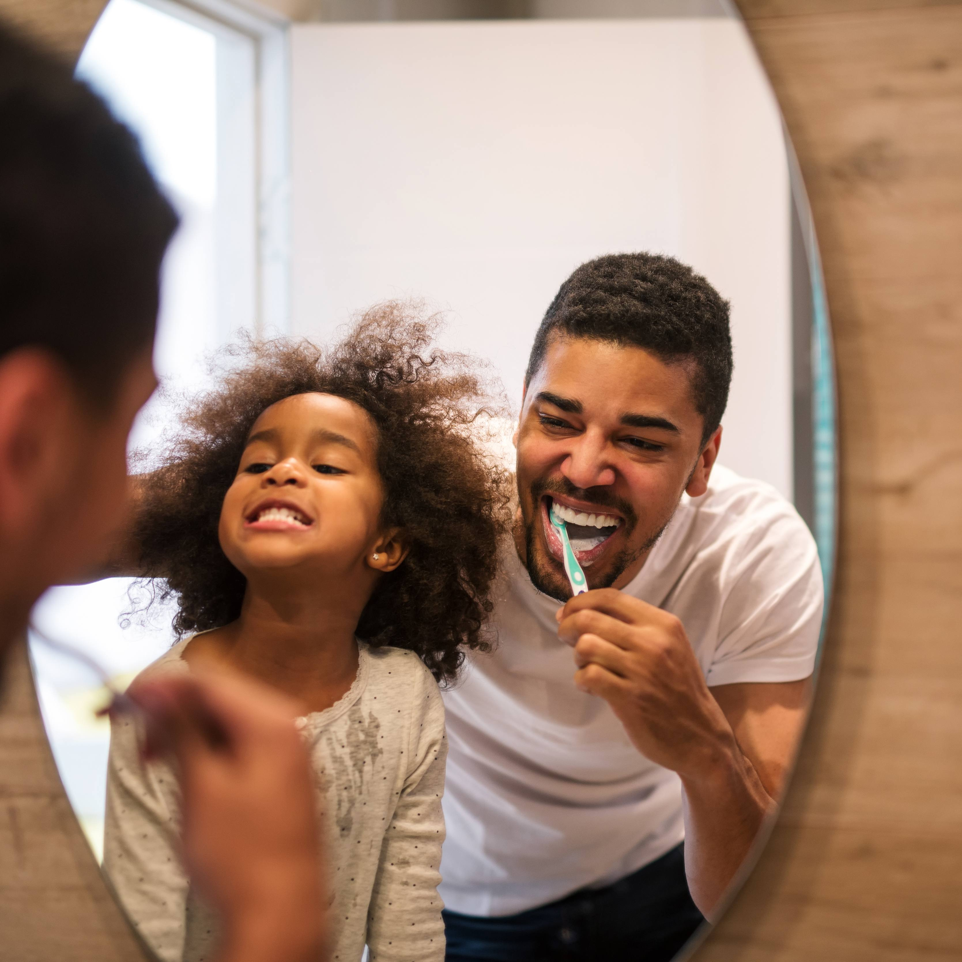 a father and young daughter brushing their teeth and looking into a mirror together