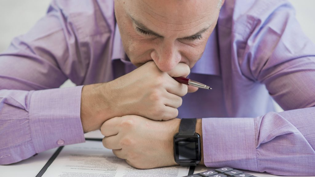 a man resting his head on his hands, holding a pen at work and looking sad, depressed or stressed in the office