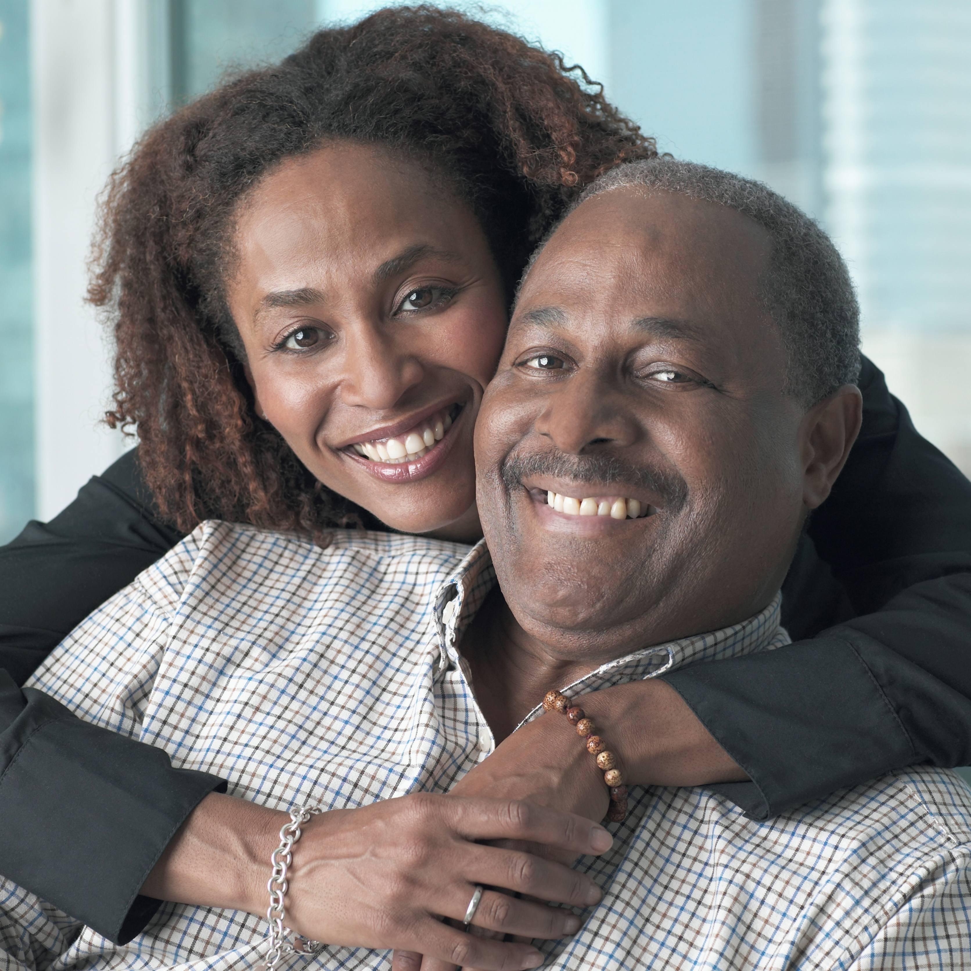 a middle-aged African-American couple smiling and hugging
