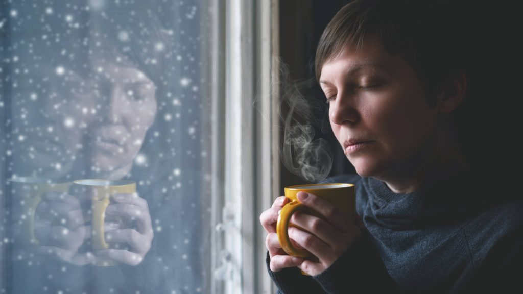 a middle-aged woman looking sad, with her eyes closed, holding a cup in both hands, standing in front of a dark window with snow falling outside