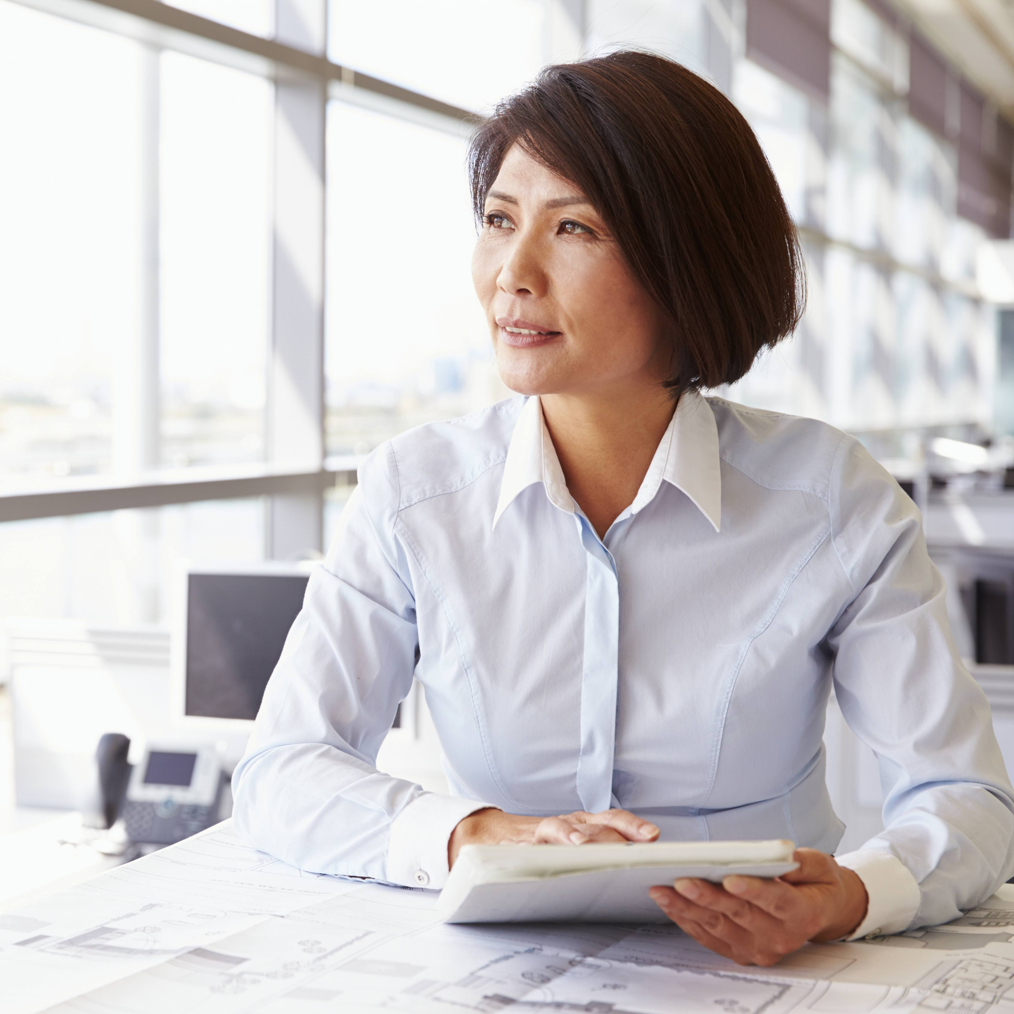 a middle-aged women sitting a an office table, holding an ipad and looking out a window