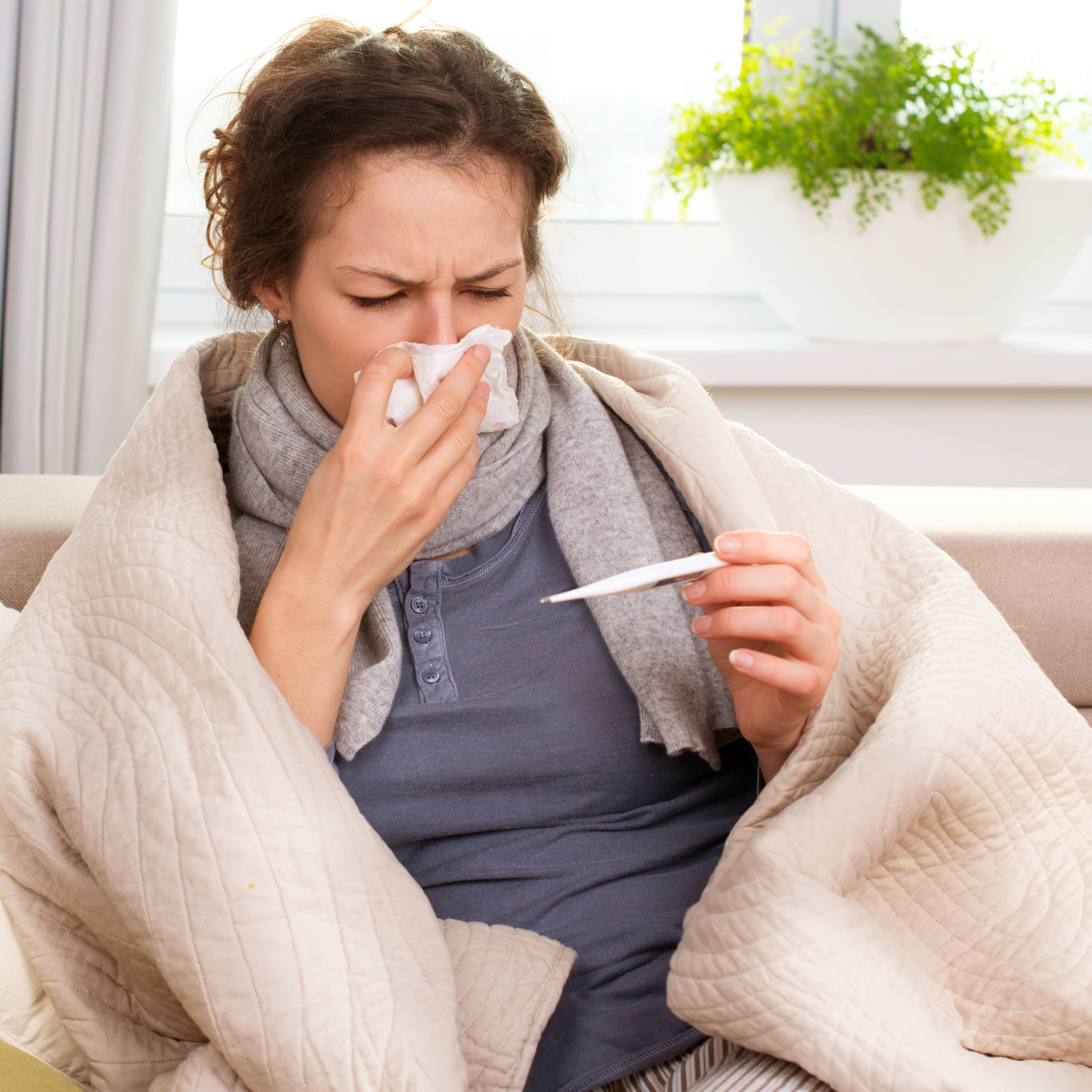 a woman wrapped in a blanket coughing, sneezing with a cold or flu and checking her temperature for a fever