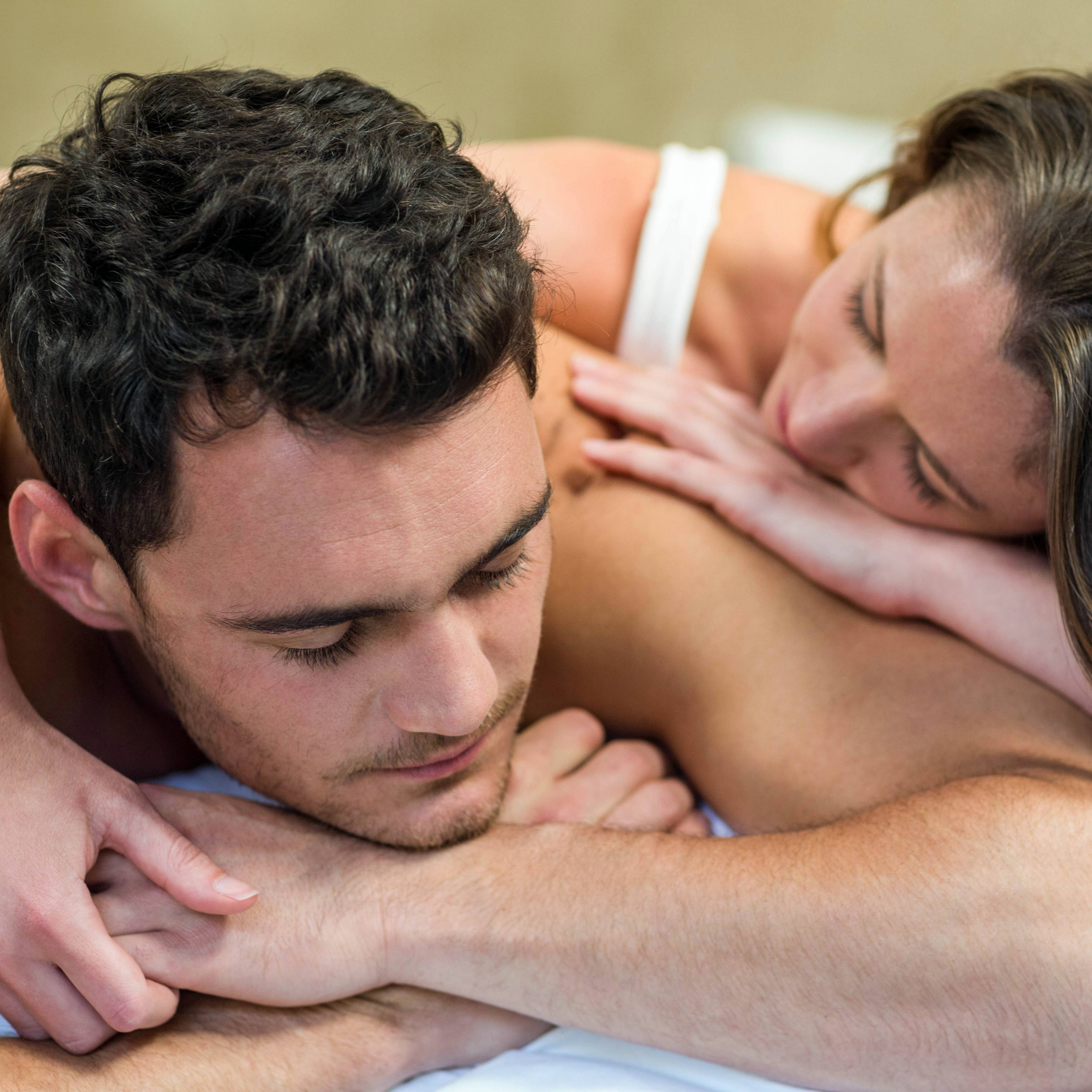 a young couple is cuddling in bed