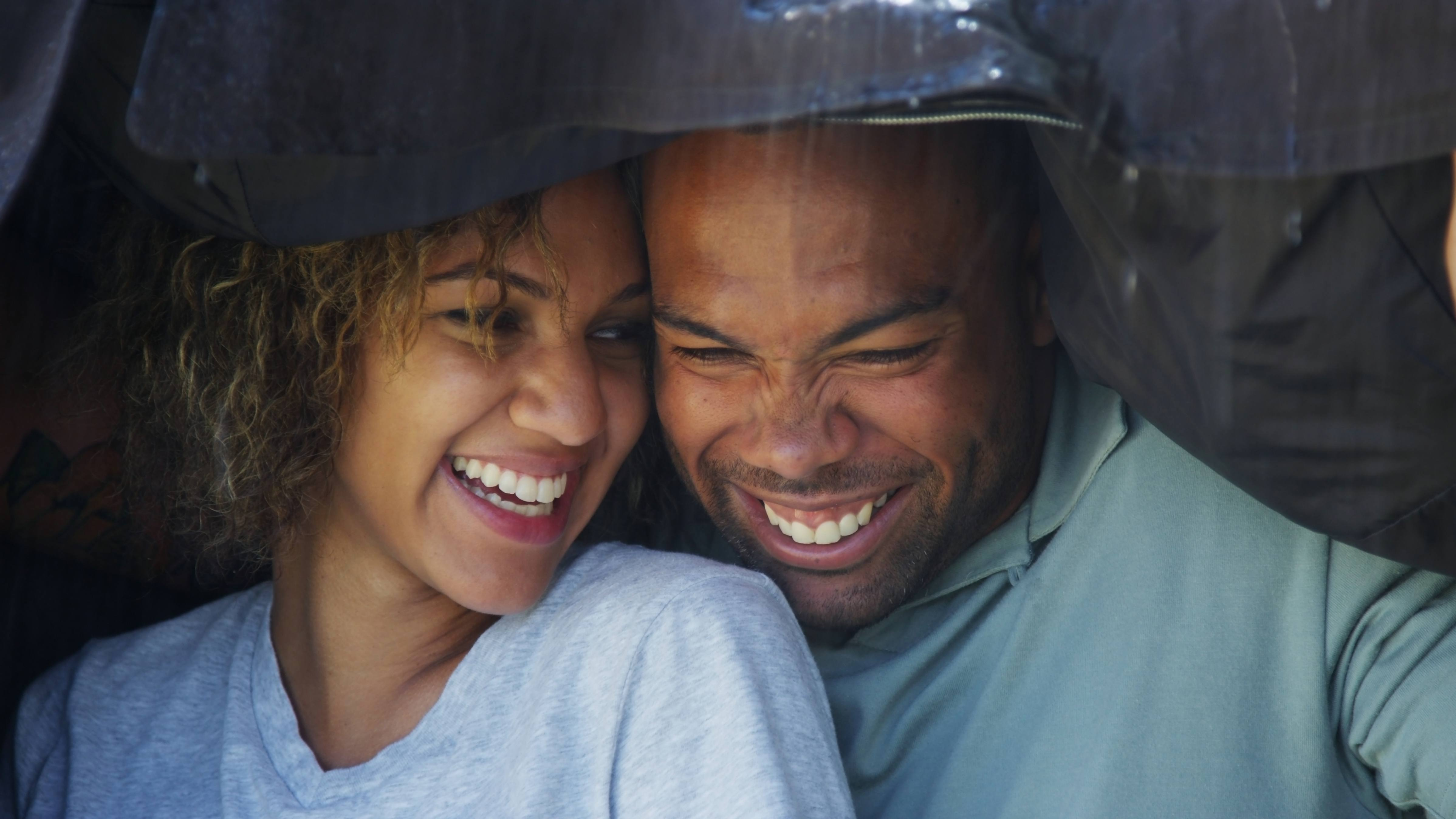 a young, happy African-American couple smiling and covering up in the rain
