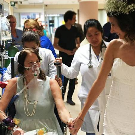 patient Amy Cierzan-Shaw and her daughter Alison in her wedding gown, holding hands in the hospital hallway