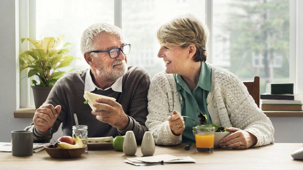 Un par de ancianos comen y sonríen sentados a la mesa en un cuarto soleado