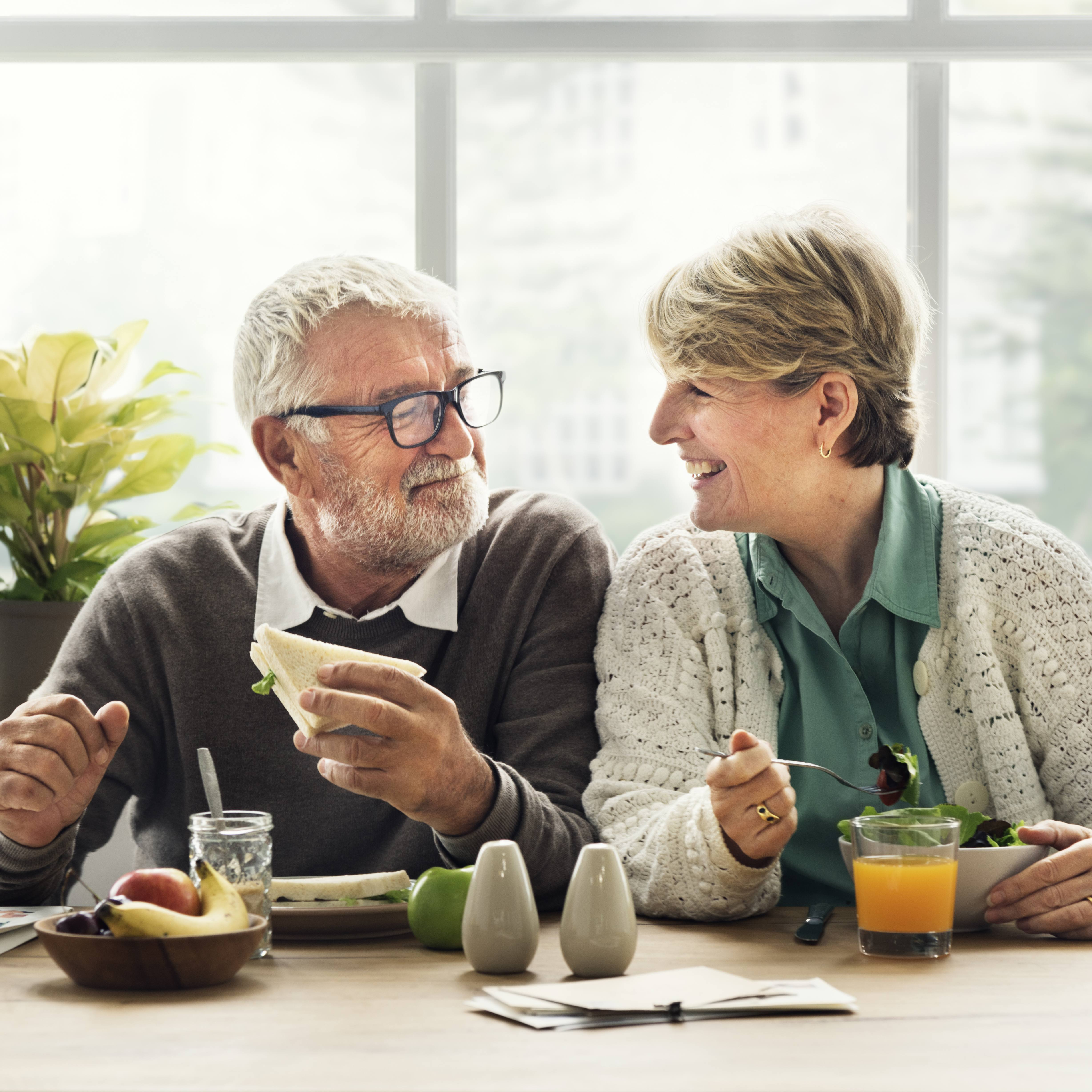 an older couple seated at a table in a sunny room, eating and smiling at one another