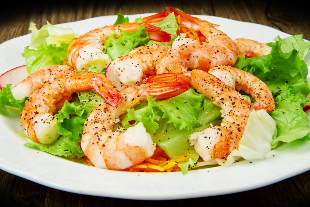 a close-up of a plate of shrimp and mixed greens