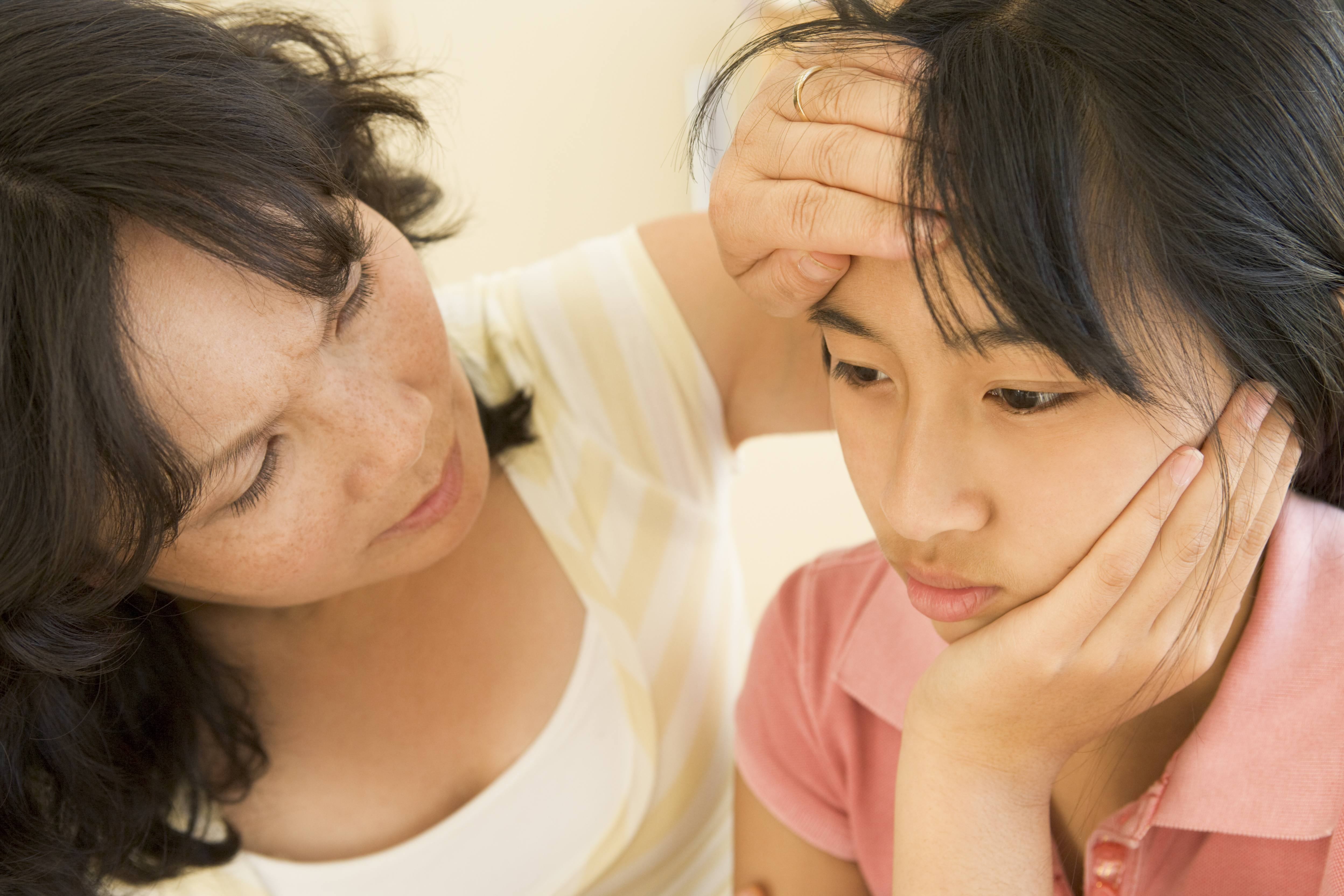a young Asian teenage girl looking sick with cold or fever and mother holding her face