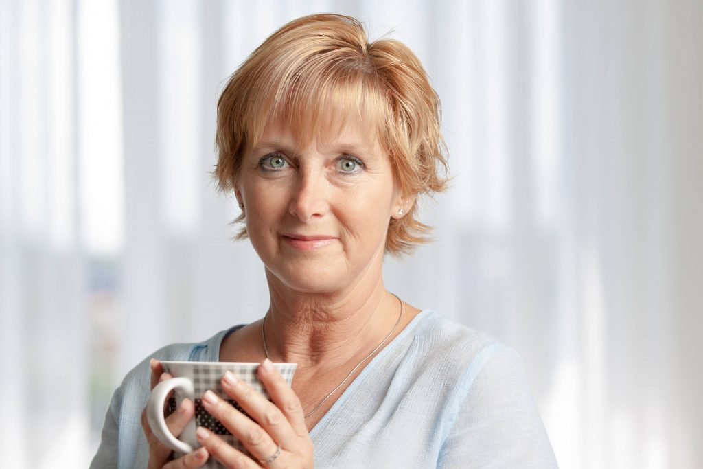 a close-up of an older woman, holding a cup in her hands, looking concerned, smiling tentatively and looking straight into the camera