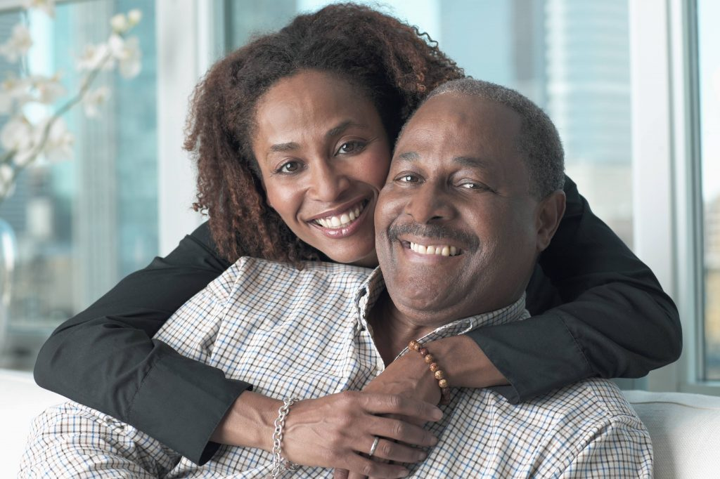 a middle-aged African American couple smiling and hugging