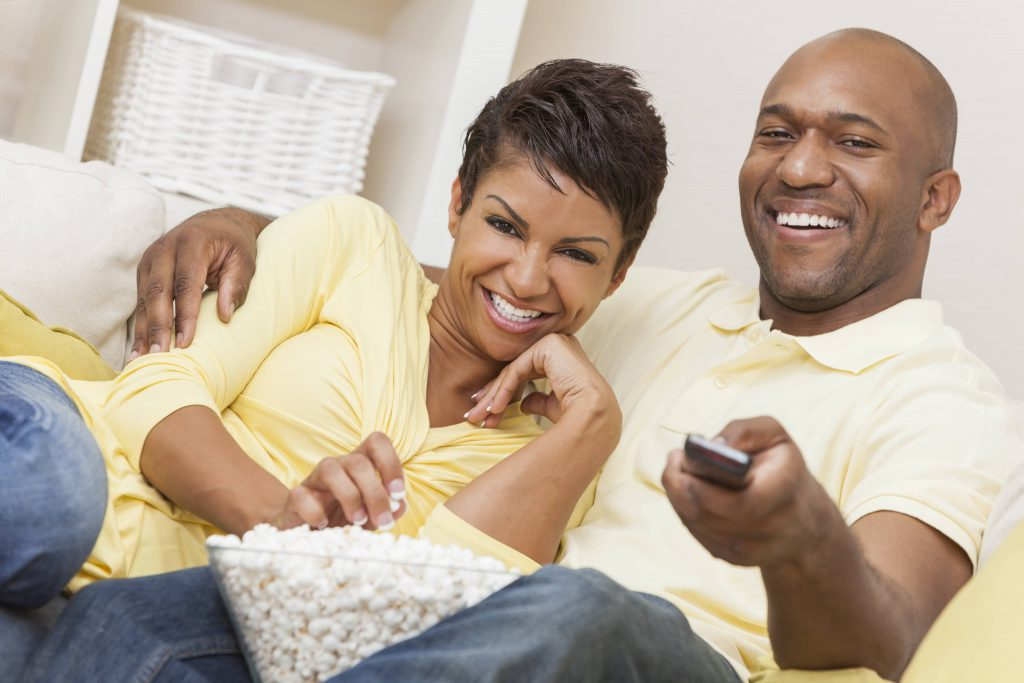 a smiling midddle-aged couple sharing a bowl of popcorn and watching TV