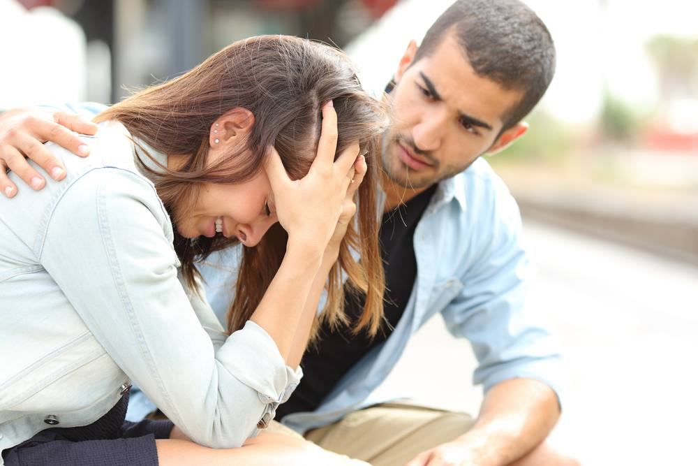 a young couple looking sad and upset sitting together