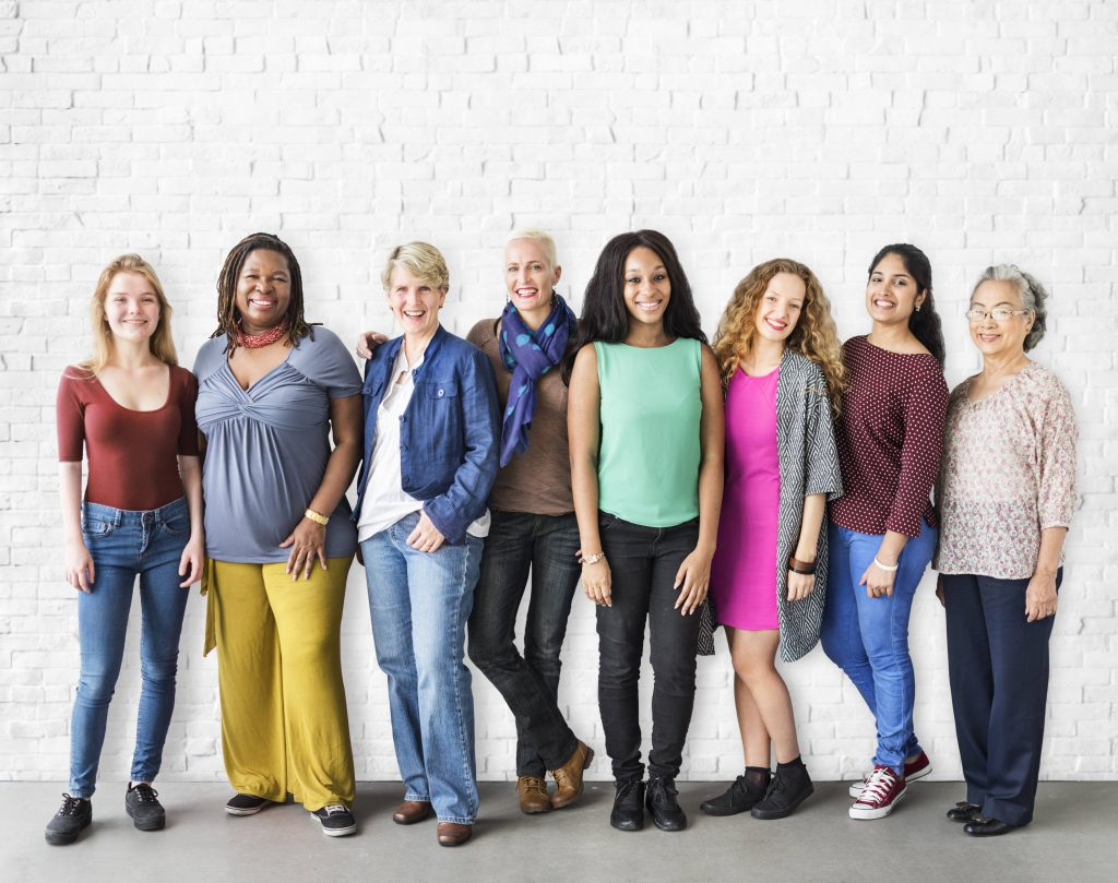 a diverse group of women standing together and smiling