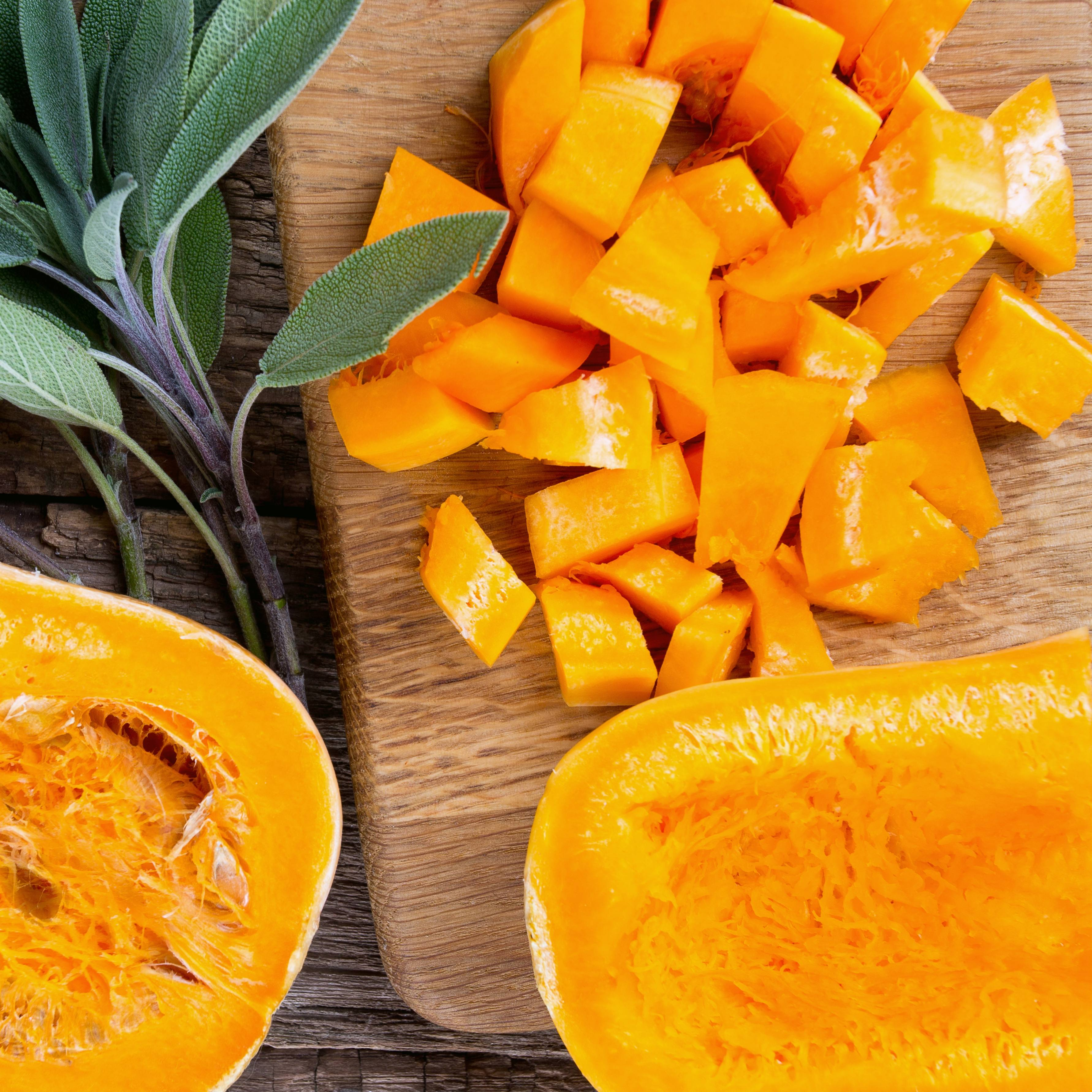 sliced, diced and cut up butternut squash on a wooden kitchen board, fresh vegetable